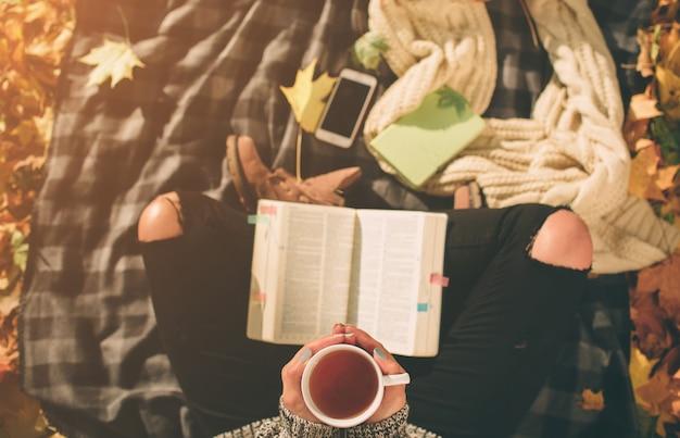 Schöne junge brünette sitzt auf einem gefallenen herbstlaub in einem park, weibliches modell trinkt tee oder kaffee und liest ein buch