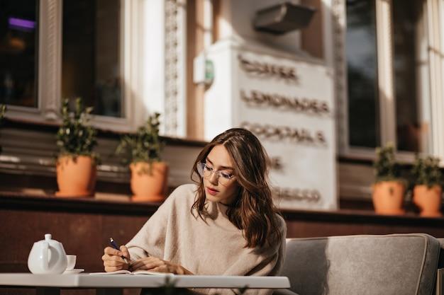 Schöne junge brünette studentin mit make-up, brille und beigem pullover, studieren, etwas notieren und eine tasse tee auf der sonnigen terrasse des stadtcafés trinken