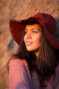 Schöne junge brünette trägt einen stilvollen hut bei sonnenuntergang in einem weinberg mit strohballen hinter ihr.