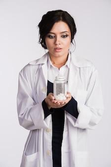 Schöne junge brünette weibliche krankenschwester oder arzt mit brille im blauen kleid und im weißen laborkittel, der eine flasche pillen hält