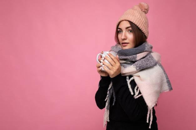 Schöne junge brunet-frau mit schwarzem pullover und warmem schal einzeln auf rosafarbenem hintergrund, die papierbecher für ein modell hält, das heißen tee trinkt und in die kamera schaut und sich erkältet. freiraum