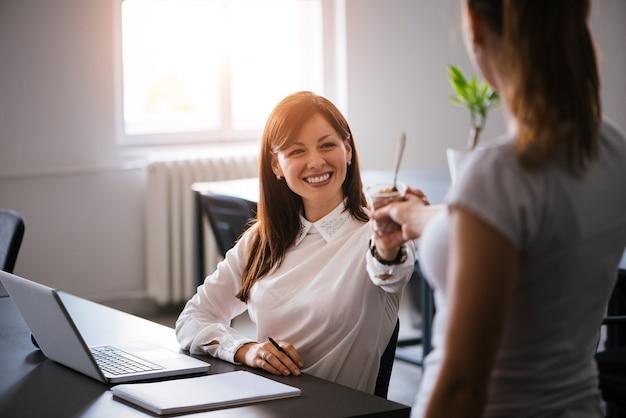 Schöne junge brunettefrau, die auffrischungseis im büro isst