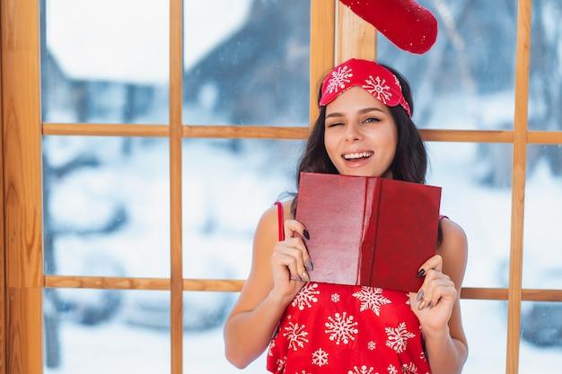 Schöne junge brunettefrau, die rote pyjamas trägt und am fenster liest