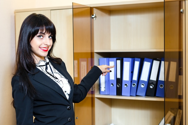 Schöne junge brunettefrau, die zu den ordnern mit dokumenten darstellt