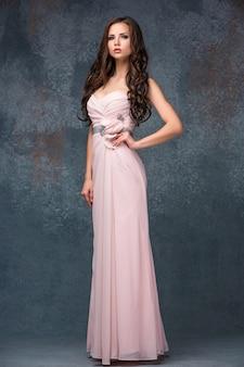 Schöne junge brunettefrau mit ihrem haar, das in ai langem rosa kleid aufwirft.