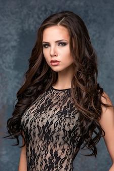 Schöne junge brunettefrau mit ihrem haar, das in einem maßwerkkleid aufwirft.