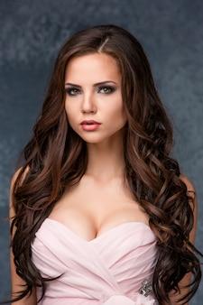 Schöne junge brunettefrau mit ihrem haar, das in einem rosa kleid aufwirft.