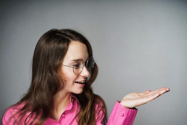 Schöne junge büroangestellte in einem rosa hemd und einer brille, die lächelt und etwas zeigt