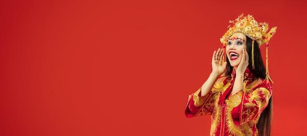 Schöne junge chinesische frau, die nationaltracht trägt und schreit