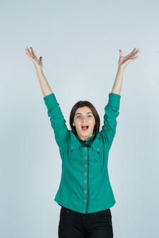 Schöne junge dame, die arme streckt, mund im grünen hemd öffnet und glückselig aussieht. vorderansicht.