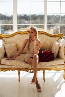 Schöne junge dame, die auf couch mit blumenstrauß der roten rosen ruht