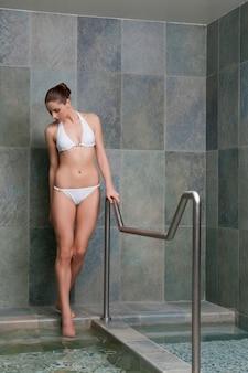 Schöne junge dame, die durch wasserbecken für kniebehandlung geht