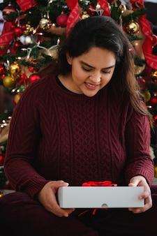 Schöne junge dame, die ein weihnachtsgeschenk hält