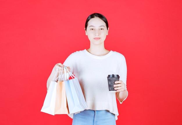 Schöne junge dame, die einkaufstasche hält und die front betrachtet