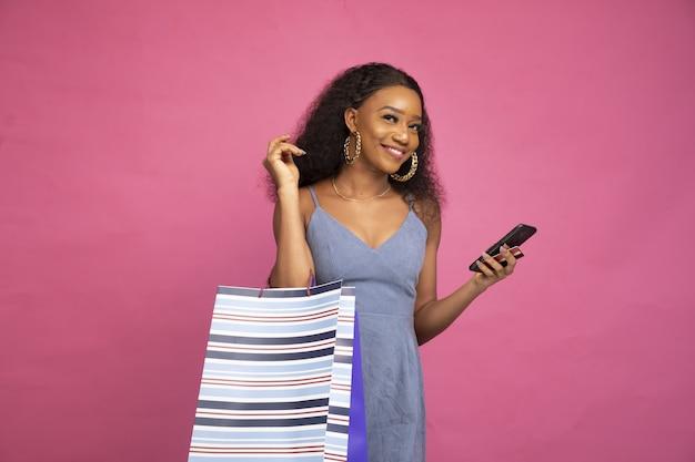 Schöne junge dame, die einkaufstaschen mit ihrem handy hält