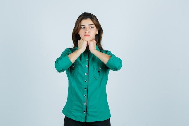 Schöne junge dame, die fäuste unter kinn im grünen hemd hält und verärgert, vorderansicht schaut.
