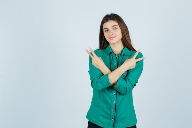Schöne junge dame, die friedensgeste im grünen hemd zeigt und fröhlich, vorderansicht schaut.