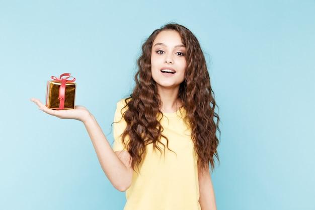 Schöne junge dame, die geschenkbox im blauen studio hält.