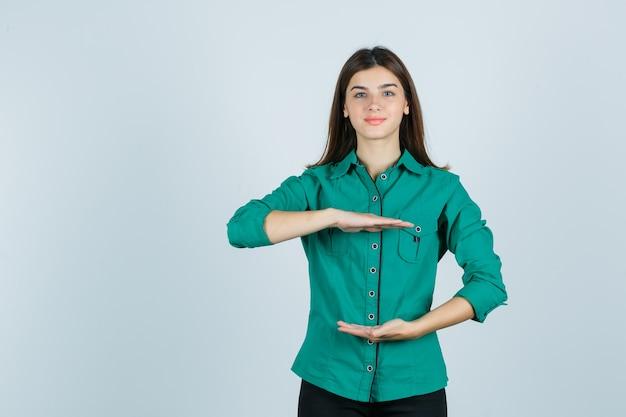 Schöne junge dame, die größenzeichen im grünen hemd zeigt und fröhlich schaut. vorderansicht.