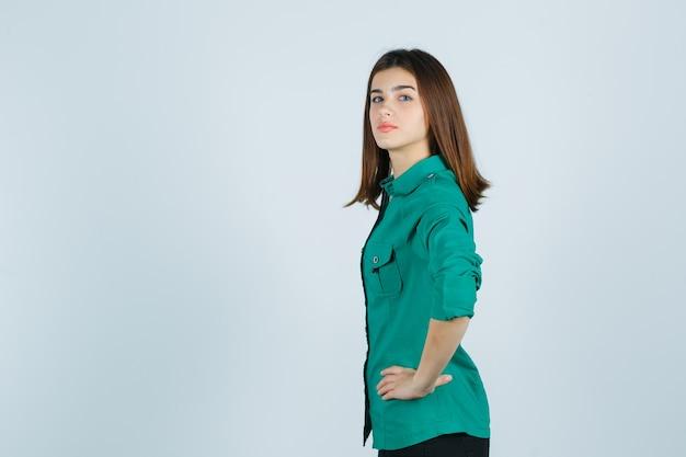 Schöne junge dame, die hände auf taille im grünen hemd hält und zuversichtlich schaut. .