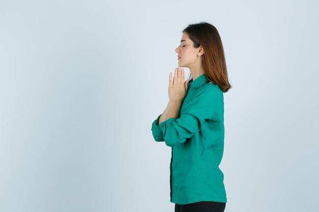 Schöne junge dame, die hände in der gebetsgeste im grünen hemd hält und hoffnungsvoll schaut. .