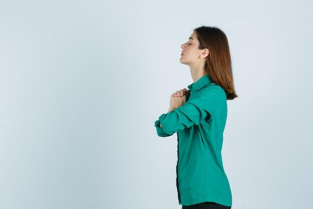 Schöne junge dame, die hände in der gebetsgeste im grünen hemd umklammert und hoffnungsvoll schaut.