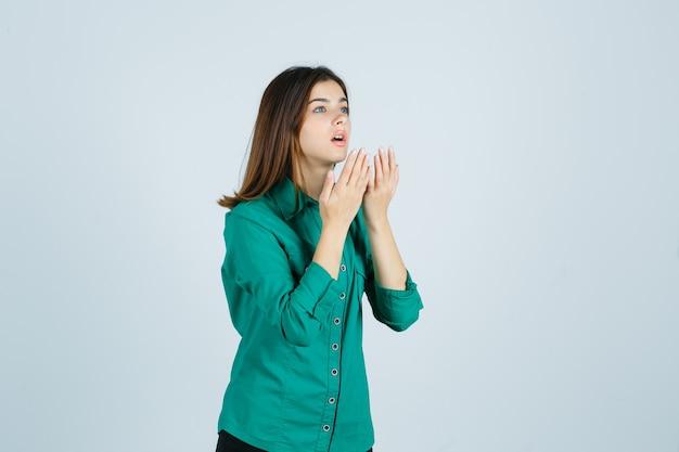 Schöne junge dame, die hände nahe offenem mund im grünen hemd hält und schockiert schaut. vorderansicht.