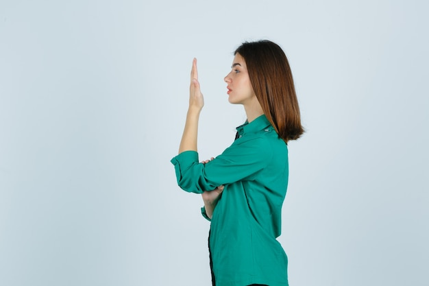 Schöne junge dame, die ihre erhabene handfläche im grünen hemd betrachtet und nachdenklich schaut. .