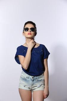 Schöne junge dame, die jeans und sonnenbrille trägt