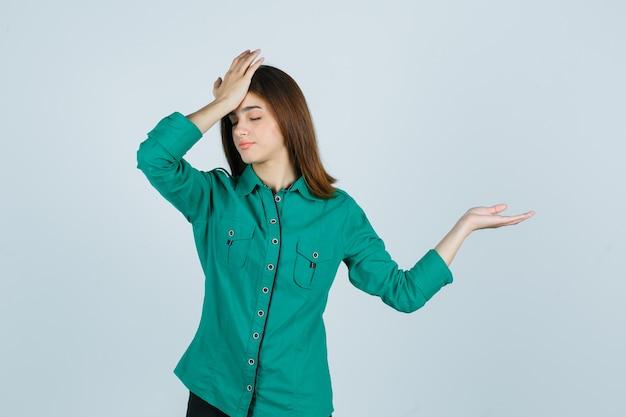 Schöne junge dame, die kopfschmerzen fühlt, während palme im grünen hemd beiseite spreizt und müde, vorderansicht schaut.