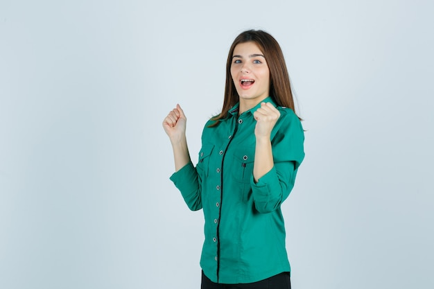 Schöne junge dame, die siegergeste im grünen hemd zeigt und glückliche vorderansicht schaut.