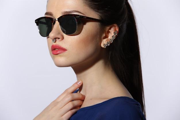 Schöne junge dame, die sonnenbrille trägt