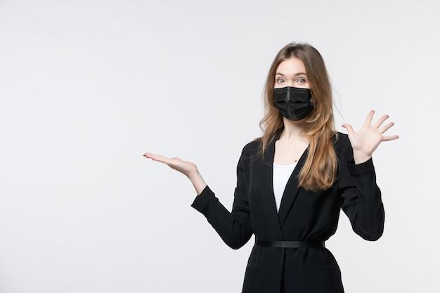 Schöne junge dame im anzug, die eine chirurgische maske trägt und auf etwas zeigt, das fünf auf weiß zeigt