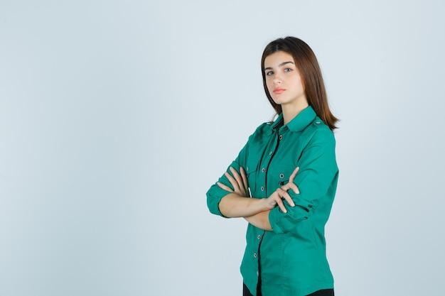 Schöne junge dame im grünen hemd, das arme verschränkt hält und ernsthafte vorderansicht sieht.