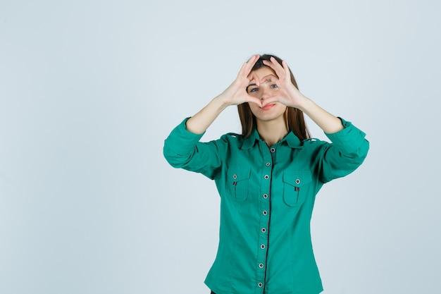 Schöne junge dame im grünen hemd, das herzgeste macht und fröhlich, vorderansicht schaut.