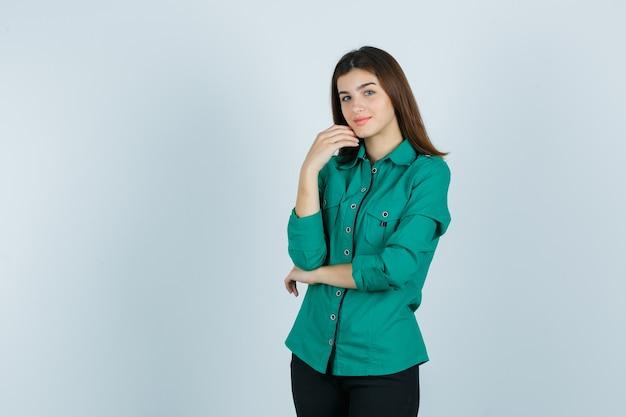 Schöne junge dame im grünen hemd, das ihr kinn mit der hand berührt und zart, vorderansicht schaut.