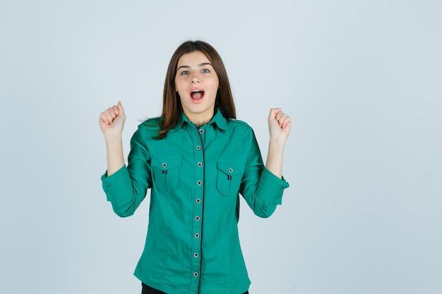 Schöne junge dame im grünen hemd, das siegergeste zeigt und glückliche vorderansicht schaut.