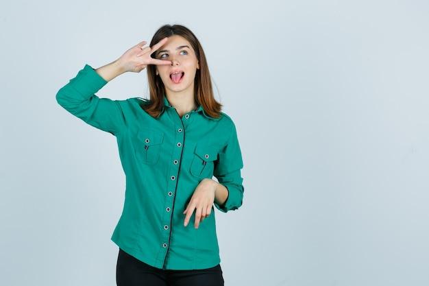 Schöne junge dame im grünen hemd, das v-zeichen auf auge zeigt und froh schaut, vorderansicht.
