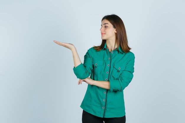 Schöne junge dame im grünen hemd, das vorgibt, etwas zu halten und selbstbewusst, vorderansicht zu schauen.