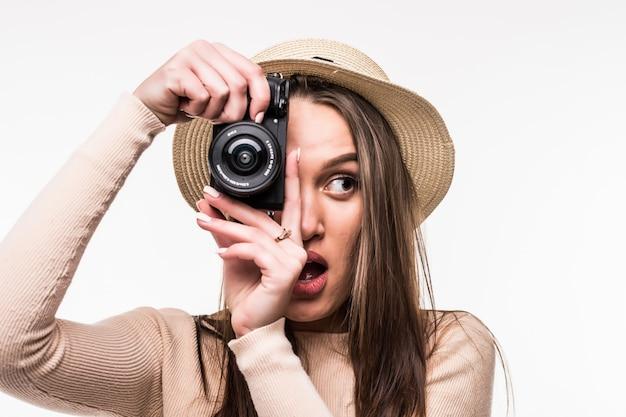 Schöne junge dame im hellen t-shirt und im hut macht foto auf retrokamera lokalisiert auf weiß