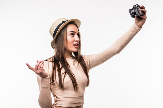 Schöne junge dame im hellen t-shirt und im hut macht selfie auf retrokamera lokalisiert auf weiß