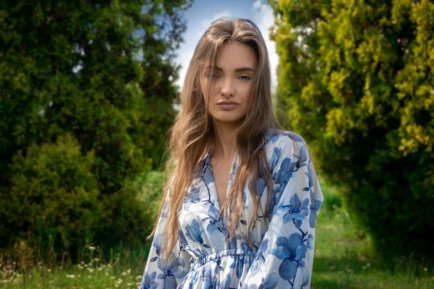 Schöne junge dame im kleid mit blumendruck, der die kamera auf den grünen garten betrachtet