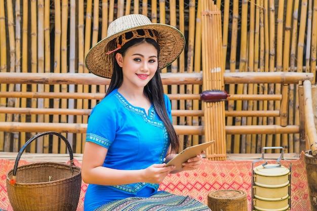 Schöne junge dame in einem traditionellen thailändischen kleid mit einer tablette, um kundenbestellungen zu erhalten.