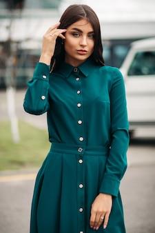 Schöne junge dame mit langen gekräuselten haaren, die stilvolles kleid tragen, während sie an der kamera im freien aufwirft. lifestyle-konzept