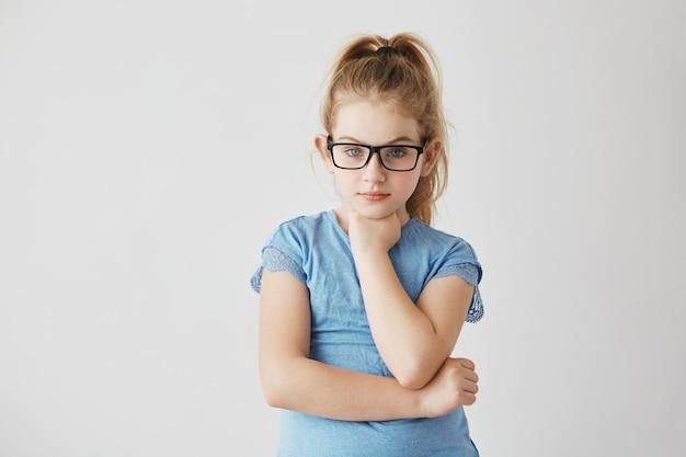 Schöne junge dame mit strahlend blauen augen und hellem haar, das in gläsern mit hand unter ihrem kinn und ernstem gesichtsausdruck aufwirft.