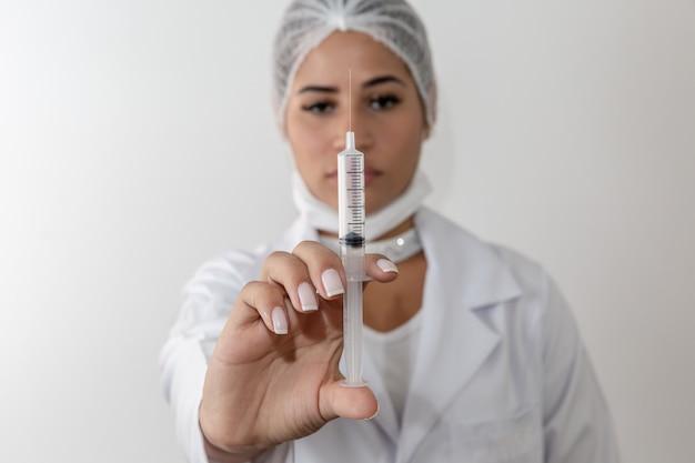 Schöne junge doktorfrau im medizinischen weißen mantel und eine schutzmaske und eine spritze.