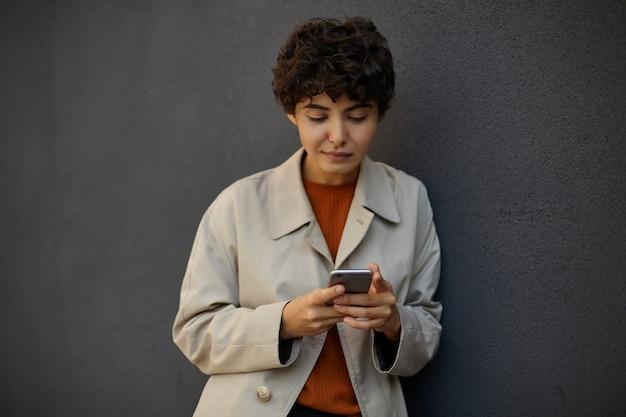Schöne junge dunkelhaarige lockige frau mit lässiger frisur, die über schwarzer betonwand steht und soziale netzwerke mit ihrem smartphone prüft und bildschirm mit ruhigem gesicht betrachtet