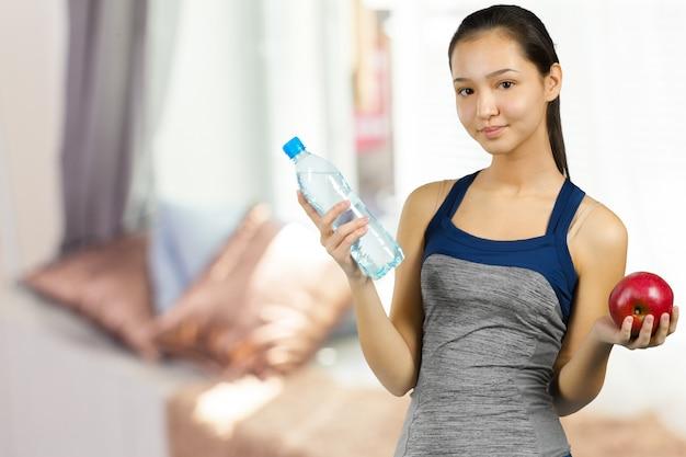 Schöne junge eignungsfrau mit perfekter körperform süßwasser trinkend