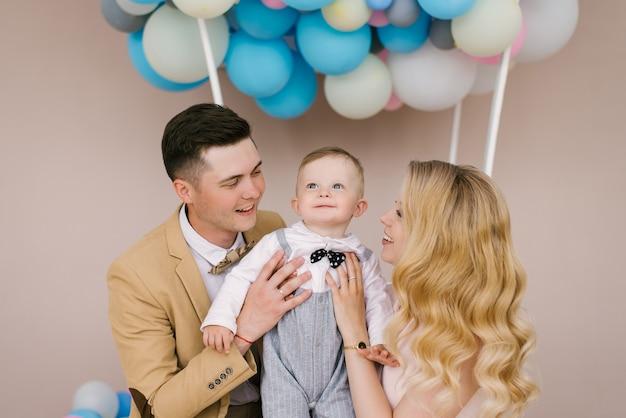 Schöne junge eltern lächeln mit ihrem einjährigen kind zu hause