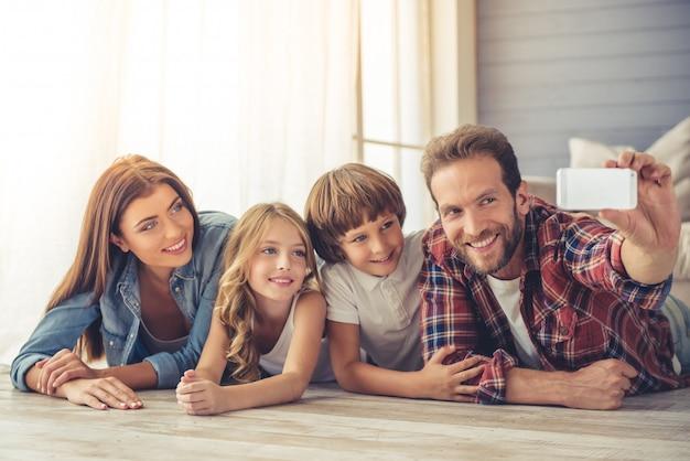 Schöne junge eltern und ihre kinder machen selfie